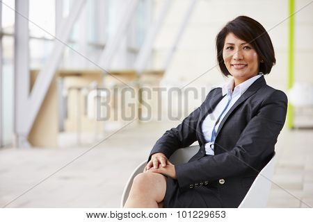 Portrait of smiling Asian businesswoman, sitting