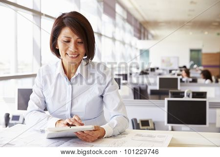 Female architect at work in an office using tablet computer