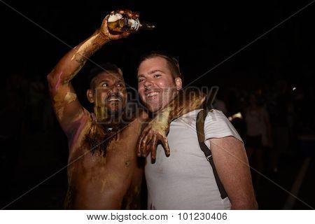 Reveler pours beer over friend's head