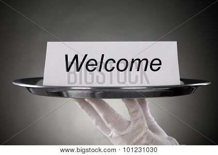 Waiter Holding Plate With Welcome Text On Paper