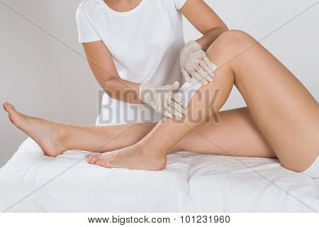 Beautician Waxing Leg Of Woman