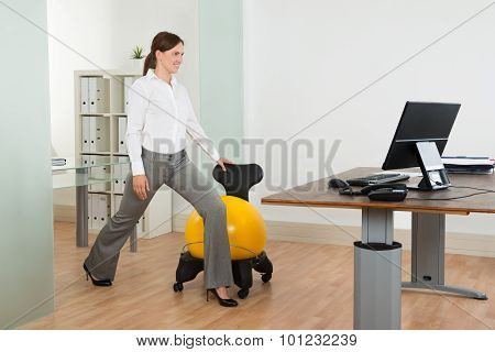 Businesswoman Exercising With Pilates Ball On Chair