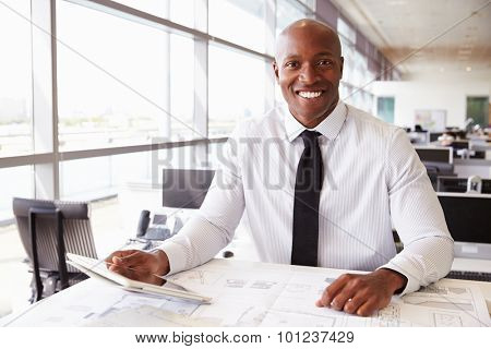 African American architect at work, smiling to camera