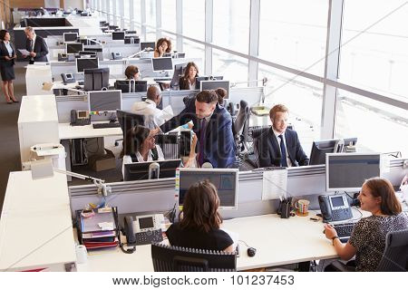 Manager in discussion with coworker in an open plan office