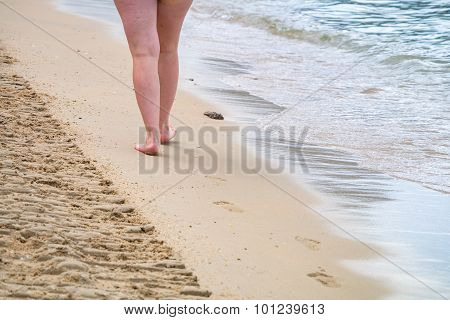 Women Legs Walking On The Beach