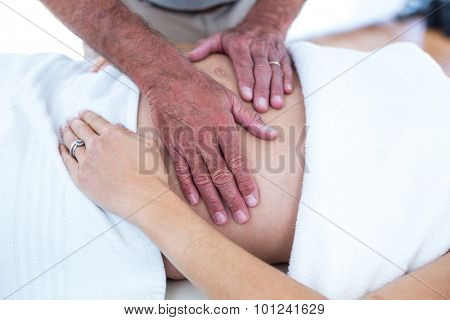 Cropepd image of masseur massaging pregnant woman lying on bed in spa