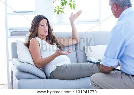 Pregnant woman talking with psychiatrist while sitting on sofa