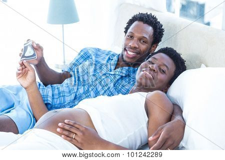 Portrait of happy husband and wife holding xray while relaxing on bed
