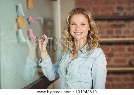 Smiling businesswoman holding marker by glass board in creative office