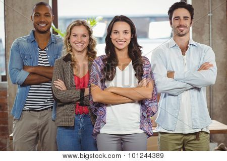 Portrait of happy business people with arms crossed standing in creative office