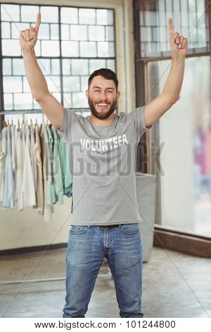 Happy man with arms raised standing in office
