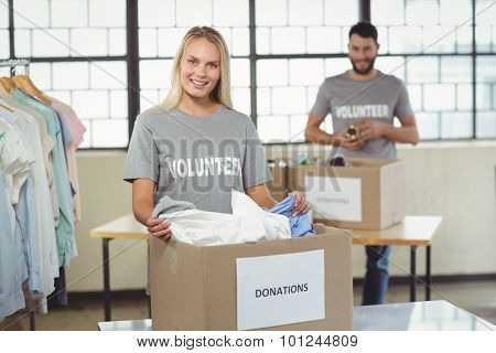 Portrait of smiling woman separating clothes from donation box in office