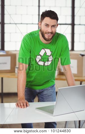Portrait of man in recycling symbol tshirt working on laptop in creative office