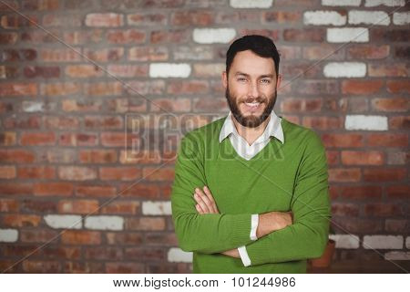 Portrait of businessman standing with arms crossed in creative office