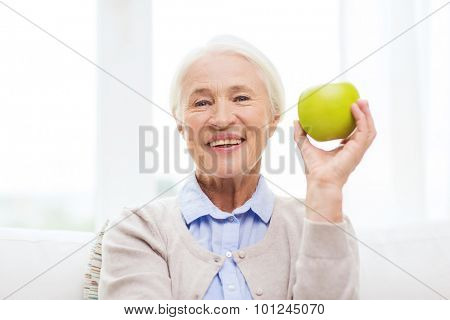 age, healthy eating, food, diet and people concept - happy smiling senior woman with green apple at home