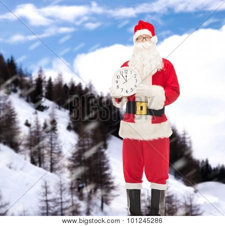 christmas, holidays and people concept - man in costume of santa claus with clock showing twelve over snowy mountains background