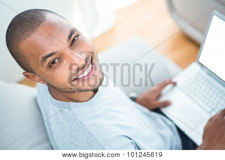 Cheerful young man with laptop on sofa at home