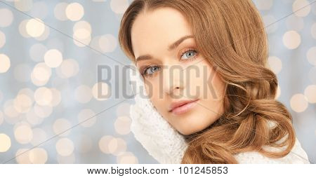 winter holidays, christmas, beauty, skincare and people concept - happy young woman in red mitten touching her face over blue lights background