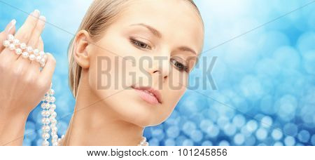 beauty, luxury, people, holidays and jewelry concept - beautiful woman with sea pearls beads in hand over blue lights background
