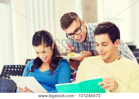 education, high school, teamwork and people concept - group of smiling students with notebook sitting in lecture hall and writing
