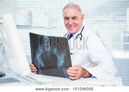 Portrait of doctor with xray sitting in front of computer at clinic