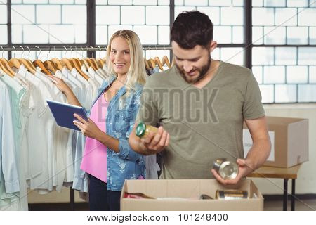 Man separating products while woman holding digital tablet in background