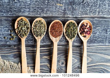 Composition with tea in wooden spoon on dark wooden background