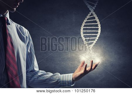 Close up of male hand holding DNA molecule in palm