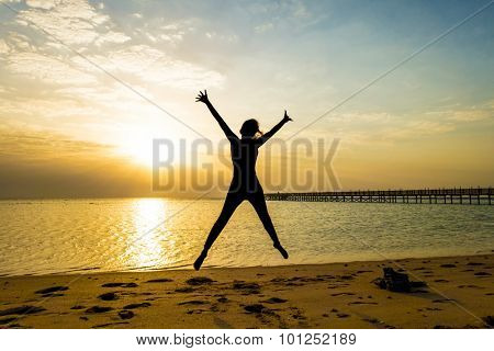 Silhouette of a happy young woman jumping against beautiful sunrise