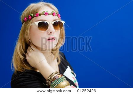 Blond girl in sunglasses with wreath of flowers and bangles