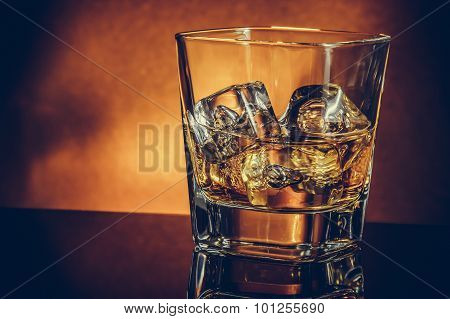 Glass Of Whiskey On Black Table With Reflection And Gold Background, Warm Atmosphere