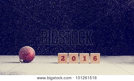 2016 New Year Background With Snow Falling Onto A Red Christmas Bauble And Row Of Four Wooden Blocks