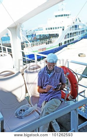 Elderly man sitting on a ship