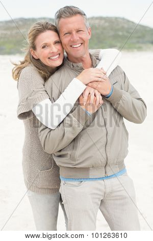 Smiling couple holding one another at the beach