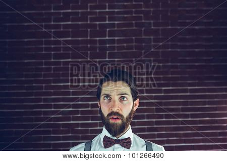 Confused stylish man looking away against brick wall