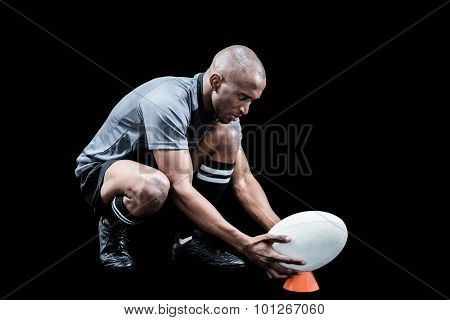 Rugby player keeping ball on kicking tee against background