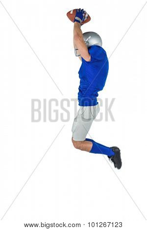 Full length of American football player catching ball in mid-air against white background
