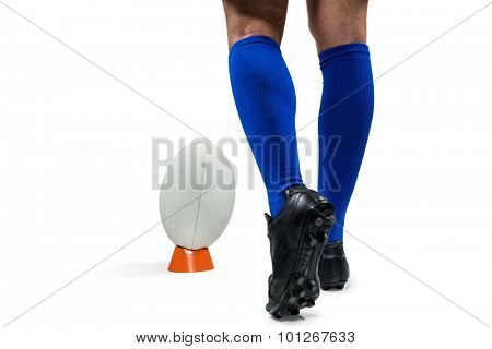 Low section of rugby player about to kick the ball against white background