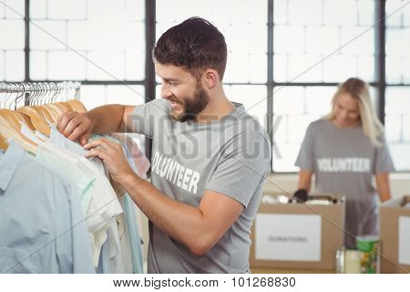 Happy man choosing clothes for donation with woman man in background