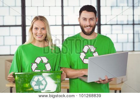 Portrait of smiling volunteers in recycling symbol tshirts in creative office