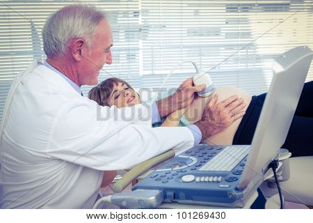 Male doctor doing ultrasound test on pregnant woman in hospital