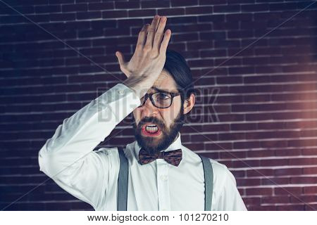 Angry man with head in hand against brick wall