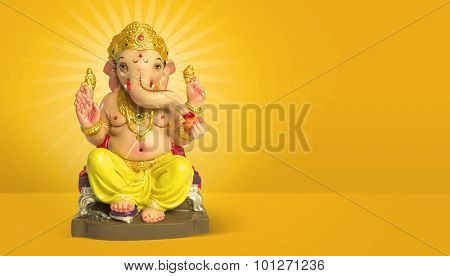 A colorful statue of Ganesha Idol on plain bright yellow background. Clear space for text or headline.