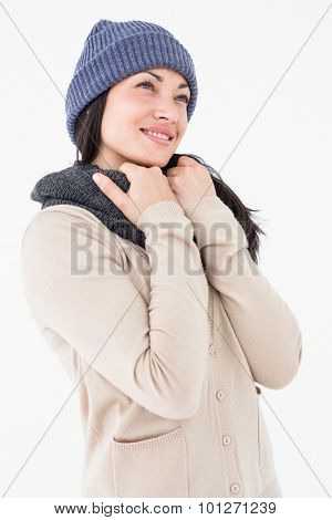 Attractive brunette looking up wearing warm clothes on white background