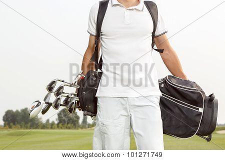 Man carrying his golf bag across course
