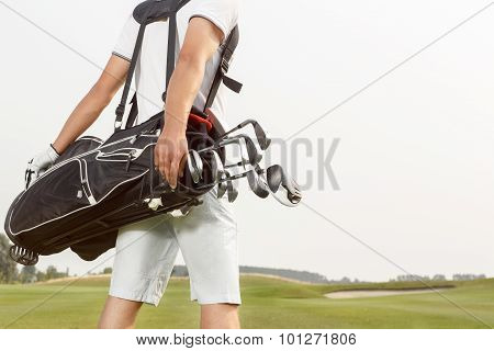 Man carrying his golf bag across course