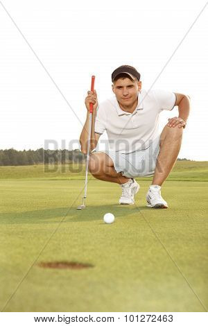 Golfer crouching and eyeing up a putt