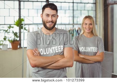 Portrait of cheerful volunteer with arms crossed standing in office
