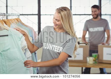Happy volunteer choosing clothes for donation with man in background