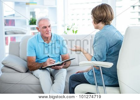 Doctor writing in book while sitting by patient at home